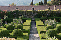 The lemon garden towards a stone wall draped in wisteria and crowned with classical urns