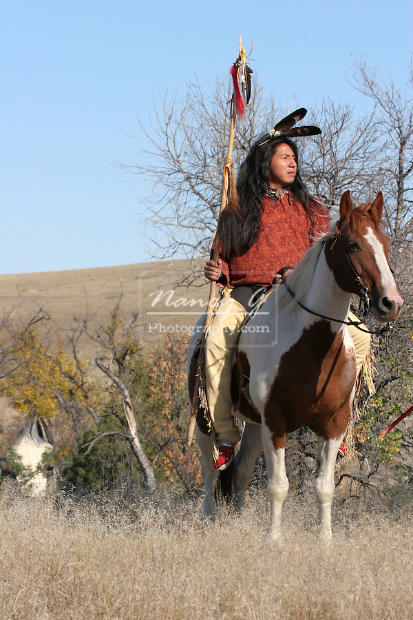 A Native American Sioux Indian on Horseback standing guard above the tipi village in the valley