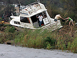 "John Pope (C) hands his wife Shirley Pope (R), of Pensacola, property they are salvaging from their 40 foot boat that landed on abandonded railroad tracks during Hurrican Ivan September 16,2004.  ""This is it,"" said John Pope of what was left of his boat as he unloaded his belongings.  Son-in-law Chris Sterner (L) looks at other boats in Bayou Chico that were destroyed or damaged."