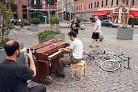"New York, NY -  22 June 2010- A man plays ""Somewhere over the Rainbow"" with one hand while eating fresh strawberries with the other, while his friend records it with a cell phone. Gansvoort Plaza in the Meat Packing District of Manhattan... ""Play Me I'm Yours"" is a musical installation by British artist Luke Jerram who has been touring the project globally since 2008. From 9am-10pm each day, 60 pianos will be available to play across New York City. Presented by Sing for Hope they are located in public parks, streets and plazas the pianos will be available until 5th July for any member of the public to play and engage with."