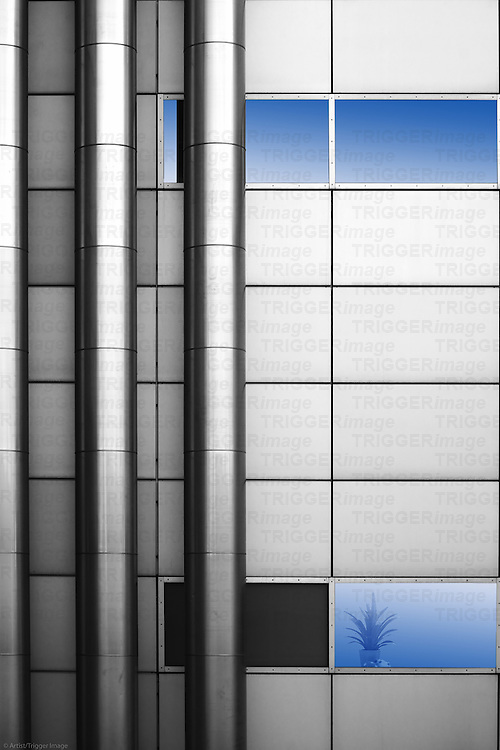 The abstract photography and installation of stainless steel pipes at a sheet metal facade with a flower pot.