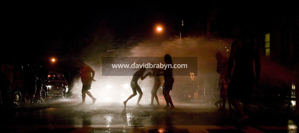 2 August 2006 - New York City, NY - People play in the water gushing from an open fire hydrant in Harlem in New York City, USA, on the hottest day of one of the summer heatwaves.