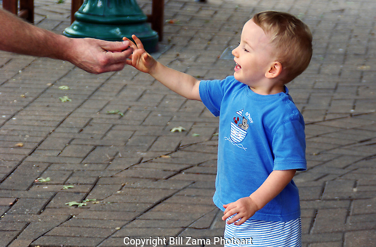 Young boy taking an acorn from his father
