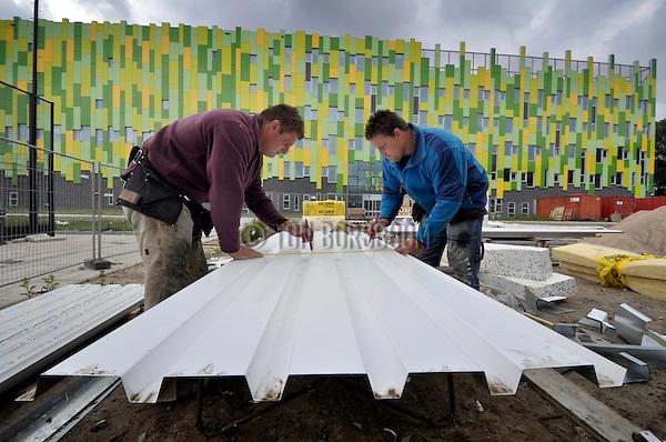 UTRECHT - In Utrechtse werken medewerkers van Cladding Partners uit Oosterhout aan de gevel van een door PBO Bouw gebouwde turnhal. Het in opdracht van de gemeente door Nl Architects ontworpen complex gaat ruimte bieden aan Turn4U, een bundeling van vier Utrechtse turnverenigingen. De turnhal die 40 bij 25 meter groot wordt, en komt te liggen naast het multifunctionele centrum Nieuw Welgelegen(op de achtergrond zichtbaar)is gebouwd volgens de eisen van het het NOC-NSF, en moet rond de zomervakantie klaar zijn. COPYRIGHT TON BORSBOOM