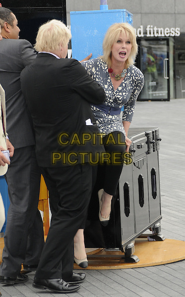 BORIS JOHNSON (Mayor of London) & JOANNA LUMLEY.The launch of the old furniture recycling scheme, The Scoop, More London, the Queen's Walk, London, England..July 12th, 2010.full length black suit grey gray white print top blue waist belt trousers leggings profile sit sitting gesture funny mouth open.CAP/CAN.©Can Nguyen/Capital Pictures.