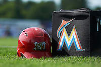 Batavia Muckdogs batting helmet and Miami Marlins ball bag in the outfield grass during the teams first official practice on June 15, 2013 at Dwyer Stadium in Batavia, New York.  (Mike Janes/Four Seam Images)