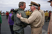 "United States President George W. Bush greets Rear Admiral John Kelly on the flight deck after a successful trap aboard USS Abraham Lincoln (CVN 72) in a S-3B Viking assigned to the Blue Wolves of Sea Control Squadron Three Five (VS-35) designated ""NAVY 1"" on May 1, 2003.   President Bush is the first sitting President to trap aboard an aircraft carrier at sea. The President is conducting a visit aboard ship to meet with the Sailors and will address the Nation as Lincoln prepares to return from a 10-month deployment to the Arabian Gulf in support of Operation Iraqi Freedom. <br /> Credit: United States Navy via CNP"