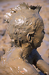 A073TX Child  playing in thick mud with head and body covered by brown mud