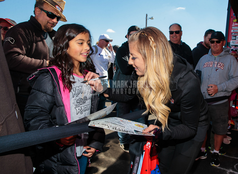 Feb 23, 2019; Chandler, AZ, USA; NHRA top fuel driver Leah Pritchett (right) signs an autograph for a young female fan during qualifying for the Arizona Nationals at Wild Horse Pass Motorsports Park. Mandatory Credit: Mark J. Rebilas-USA TODAY Sports