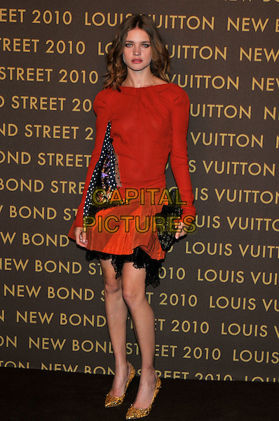 NATALIA VODIANOVA .attends the launch of the Louis Vuitton Bond Street Maison in London, England, UK, May 25th, 2010. .full length red dress polka dot sleeve long sleeved orange black clutch bag gold shoes .CAP/PL.©Phil Loftus/Capital Pictures.
