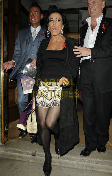 Craig Revel Horwood & Nancy Dell'Olio & guest.The Lighthouse Gala Auction, Christie's, King St., St. James's, London, England..March 19th, 2012.full length black tights jacket top skirt beige gold print bags suit blue  mouth open.CAP/CAN.©Can Nguyen/Capital Pictures.