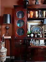In the entry hall, the walls are covered in a silk burlap by Donghia. A vintage display cabinet holds a collection of ceramic vases and a drink's tray with glass decanters. A table lamp with blue shade stands on a tall side table.
