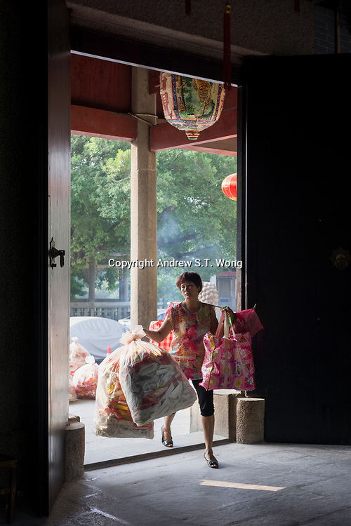 Huizhou, Guangdong province, China - A woman arrives with offerings to perform rites at Yuanmiao Taoist Temple, October 2014.