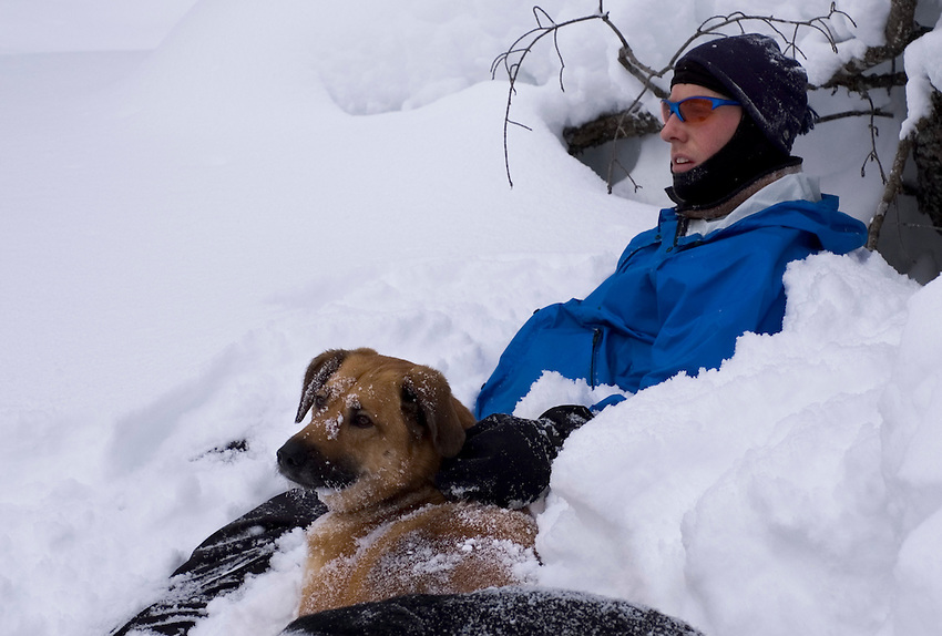 A snowshoer and his dog take a break from hiking through deep powder in the remote woods north of Ishpeming, Michigan.