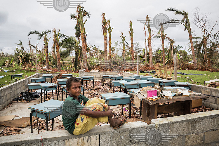 10 year old James sits on the concrete wall, all that remains of his school in Etas village. It was destroyed by Cyclone Pam on 13 March 2015. He says: 'I was in a community shelter with my parents. When the strong wind came it was very noisy, I was afraid. Then my sisters and I fell asleep. Next morning we came to our house and it was destroyed. My school was destroyed too. Now I sleep with my parents in a tent and can't attend classes'.