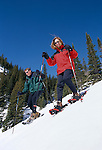 Couple snowshoeing down steep slope, Rocky Mtns, CO