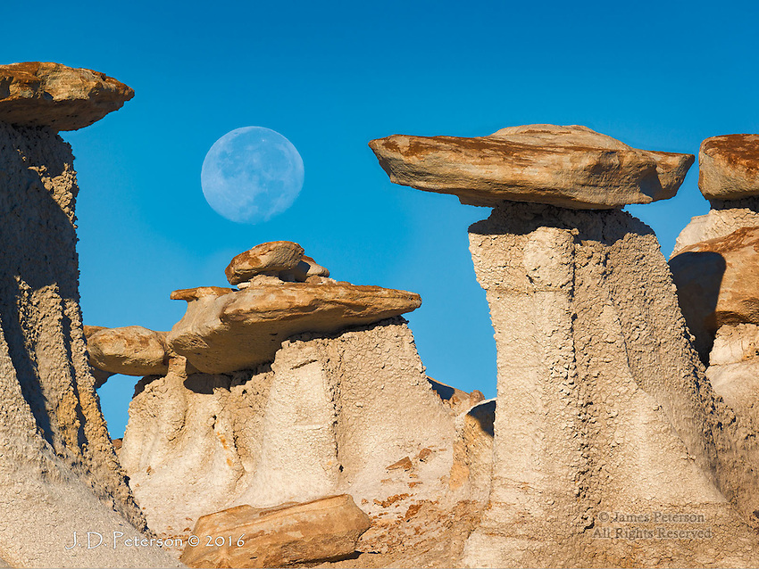 Moon over Valley of Dreams, New Mexico ©2016 James D Peterson.  The setting Moon is framed by a few of the many hoodoos in this remote Northwestern New Mexico badlands area.  This image was captured shortly after dawn on the second day after the full moon.