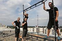 Sandra und Diana Miller bereiten sich mit dem Klettergeschirr auf den Auftritt vor, während Andreas Proksch und Etienne Herr (vlnr) die Plattform aufbauen