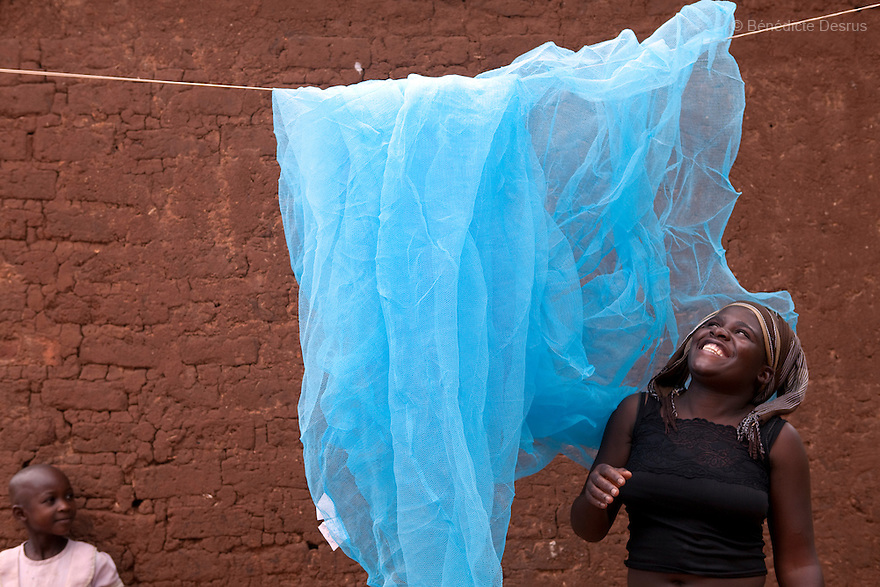 15 april 2010  Busagazi, Uganda - Joyce Musakuwona airs her mosquito net the day before hanging it up on her bedroom to prevent malaria. Malaria is a mosquito-borne infectious disease. The disease kills over a million people in the world every year, mostly children and pregnant women. Malaria transmission can be reduced preventing mosquito bites by using mosquito nets and insect repellents, or by mosquito-control measures such as spraying insecticides inside houses and draining standing water where mosquitoes lay their eggs. Photo credit: Benedicte Desrus