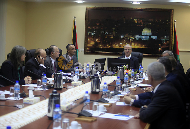 Prime Minister Rami Al-Hamdallah attends his first meeting of the new unity government cabinet, in the West Bank city of Ramallah, on June 3, 2014. The Palestinian national unity government was sworn in on Monday before Palestinian President Mahmoud Abbas in the West Bank city of Ramallah. Photo by Issam Rimawi