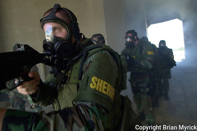 Members of the Flagler County Sheriff's Office Emergency Response Team wear gas masks as they assault a building during training.(Brian Myrick)