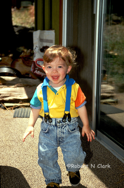 Boy wearing jeans and suspenders smiling as he walks across porch