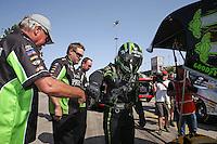 Apr. 7, 2013; Las Vegas, NV, USA: NHRA crew members with funny car driver Alexis DeJoria during the Summitracing.com Nationals at the Strip at Las Vegas Motor Speedway. Mandatory Credit: Mark J. Rebilas-
