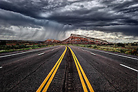 A curtain of falling rain moves over red and white striated sandstone formations along US 550 on the Zia Reservation.
