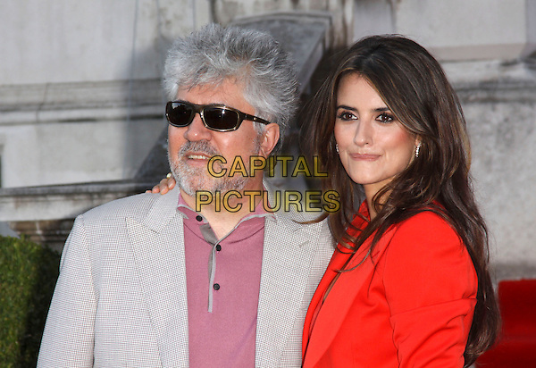"PEDRO ALMODOVAR & PENELOPE CRUZ .Attending the UK Film Premiere of ""Broken Embraces"" (Los Abrazos Rotos) at Somerset House, London, England, UK, July 30th 2009..half length sunglasses shirt t-shirt grey gray blazer suit director red jacket shoulder pads checked check gingham sunglasses beard facial hair arm around shoulder .CAP/AH.©Adam Houghton/Capital Pictures"