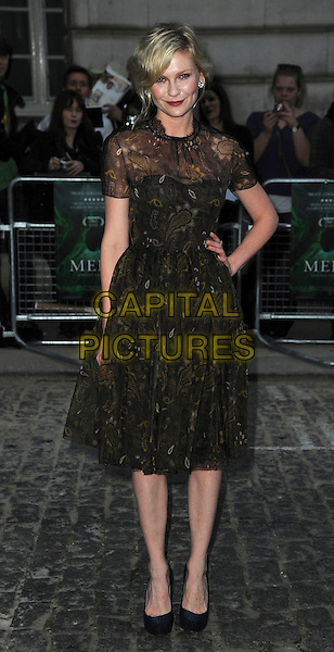 Kirsten Dunst (wearing new fashion label Honor's spring 2012 collection).UK Premiere of 'Melancholia' at the Curzon, Mayfair, London, England..September 28th 2011.full length organza paisley printed dress gold woven weave sheer black brown hand on hip.CAP/CAS.©Bob Cass/Capital Pictures.