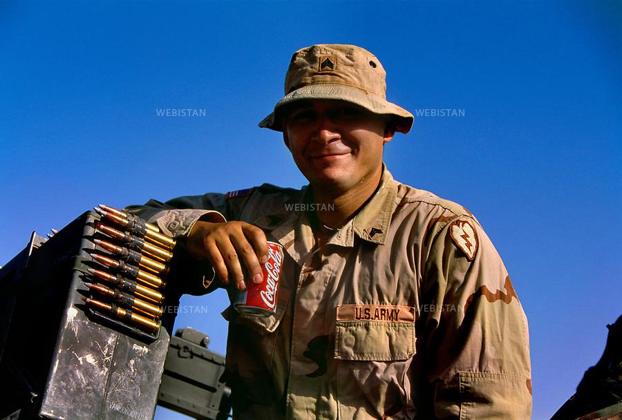2004. Afghanistan. Shkin. American soldier of the alpha company, Second Battalion, 27th Infantry Regiment drinking a Coke. Un soldat américain boit un Coca-Cola avant de partir en patrouille avec ses camarades, à bord de leur véhicule tout terrain, un Humvee, dans la zone tribale pachtoune du Waziristan.