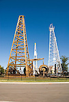 Devon Energy Oil and Gas Park at the state history museum, Oklahoma City, OK, with wooden and metal oil drilling derricks (towers) and portable oil drilling rig. In foreground the round objects are oil pumps once used in the early 20th century.
