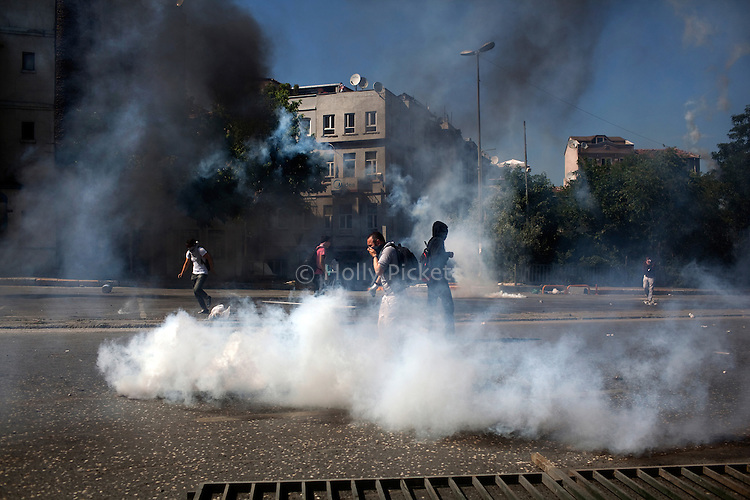Protesters run from tear gas on Tarlabasi Street, Istanbul, Turkey, June 1, 2013. What started as a peaceful sit-in to save a small park near Taksim Square from being turned into a shopping mall has turned into large-scale anti-government demonstrations in cities across Turkey.