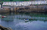 AE2KXC Porthleven harbour low tide Cornwall England. A row of white houses overlook the harbour