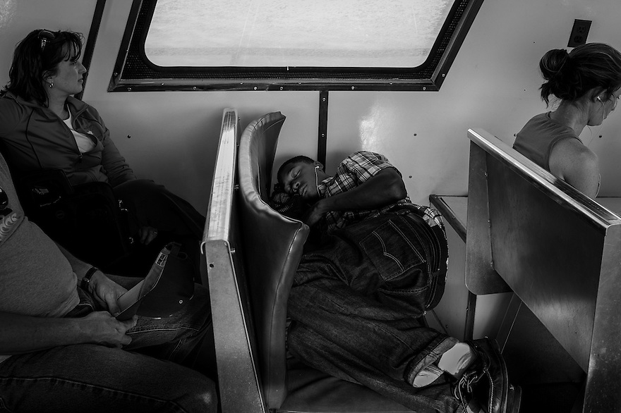 A teenager takes a nap on the ferry to Sapelo Island after attending school on the mainland. The children of Hog Hammock have been taking the ferry to the mainland and then a bus to the school after its own school closed in 1978.