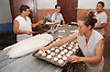 Bakers rolling out dough and shaping bread rolls in bakery in Havana; Cuba,