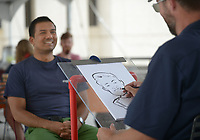 NWA Democrat-Gazette/ANDY SHUPE<br /> Prabhat Khadka, a graduate student at the University of Arkansas from Nepal, smiles Wednesday, Sept. 12, 2018, as artist Kyle Henry of Springdale draws a caricature during the University Programs Fall Fest at the Arkansas Union on campus in Fayetteville. Henry works for NWA Caricatures and draws guests at weddings, parties and events.