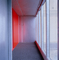 The scarlet front door opens into a corridor that has interior walls of metal and exterior walls of  glass