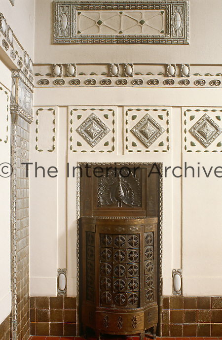 An antique copper stove is set into a wall exqusitely decorated in ornamental tiling