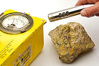 Geiger counter measuring radioactivity of uraninite with gummite, the latter a stage in the alteration of uranitite, an important ore of uranium. The gieger counter (set at 100x) is reading a little over 6000 clicks per minute (c/m), or 11 mr/hr. Typical background radiation is 30 to 40 c/m or .03 to .04 mr/hr, thus the specimen is approximately 200 times more radioactive. Grafton Center, New Hampshire.