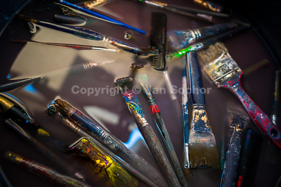 """Painting brushes are seen floating in the rinse water basin in the sign painting workshop in Cartagena, Colombia, 14 April 2018. Hidden in the dark, narrow alleys of Bazurto market, a group of dozen young men gathered around José Corredor (""""Runner""""), the master painter, produce every day hundreds of hand-painted posters. Although the vast majority of the production is designed for a cheap visual promotion of popular Champeta music parties, held every weekend around the city, Runner and his apprentices also create other graphic design artworks, based on brush lettering technique. Using simple brushes and bright paints, the artisanal workshop keeps the traditional sign painting art alive."""