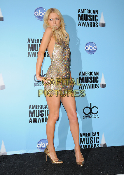 PARIS HILTON.The 2008 American Music Awards held at Nokia Theatre Live L.A. in Los Angeles, California, USA..November 23rd, 2008      .AMA AMAs full length gold sparkly mini dress shoes hands on hips beads pressroom beaded                                                   .CAP/DVS.©Debbie VanStory/Capital Pictures.