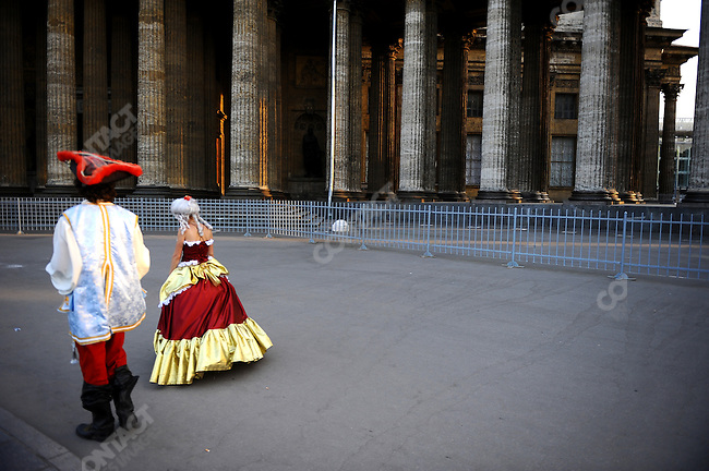 A couple dressed up in costume, making money by posing with tourists, walked passed the Kazan Cathedral in central St. Petersburg, Russia, July 7, 2010