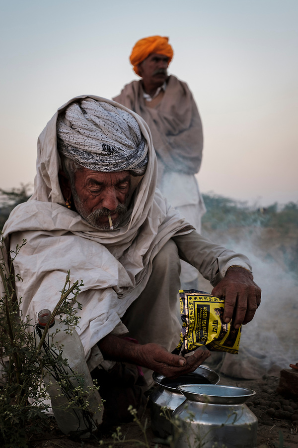 PUSHKAR, INDIA - CIRCA NOVEMBER 2016: Camel herder preparing tea  early morning in the Pushkar Camel Fair grounds. It is one of the world's largest camel fairs. Apart from the buying and selling of livestock, it has become an important tourist attraction.