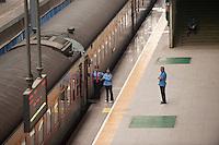 Daytime landscape view of three railway workers standing at a railroad platform at the Hankou Railway Station in Hànkǒu in the Jiānghàn Qū in Hubei Province.  © LAN