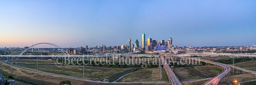 Dallas Aerial at Twillight Pano -Dallas Aerial cityscape view from south location of the city with the new Margaret McDermott Bridge at twillight. The sun was just going down when the sky lit up with some the pinks and blues of the twillight or blue hour as some called it along the Trinity river. The high rise building still had a hint of light from the sunset and you can see the freeway around the area into downtown.
