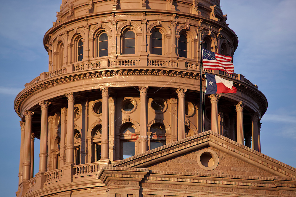 United States of America (US, USA) and Texas Flags fly over the majestic Texas State Capital Dome in Austin, Texas, USA.
