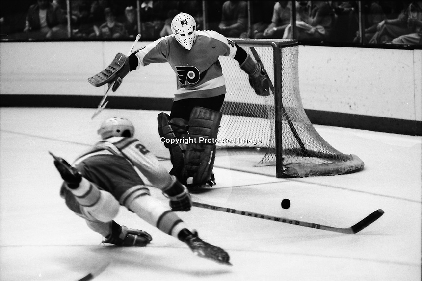Seals #2 Rick Hampton shoots on Philadelphia Flyer golie Bernie Parent. (1975 photo/Ron Riesterer)