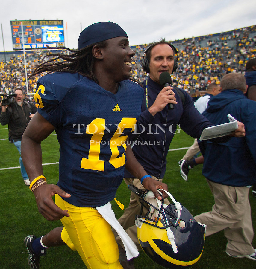 Michigan quarterback Denard Robinson (16) is chased down field by WXYT Radio's Doug Karsch after an NCAA college football game, Saturday, Sept. 4, 2010, in Ann Arbor. Michigan won 30-10. Robinson broke a school record for most yards rushing by a quarterback. (AP Photo/Tony Ding)