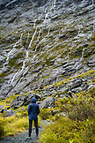 NEW ZEALAND, Fiordland National Park,Woman watching Waterfalls above the Homer Tunnel, Ben M Thomas